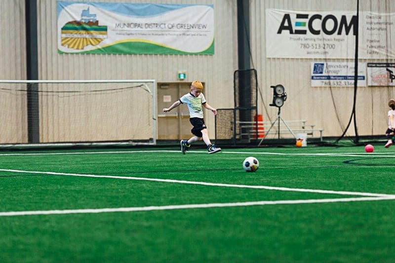 young child playing soccer indoors